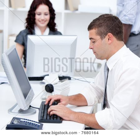 Assertive Young Business People Working At Computers
