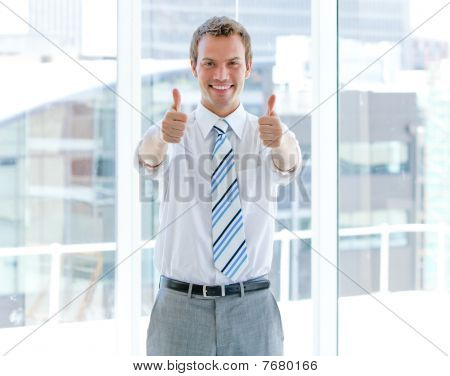 Portrait Of A Successful Businessman With Thumbs Up