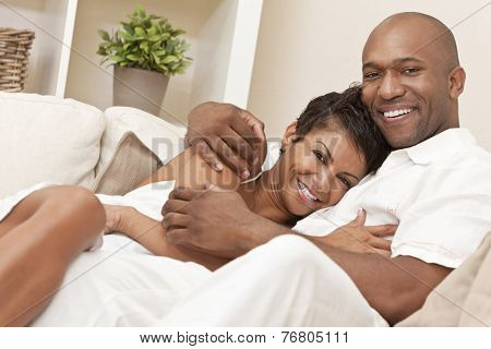 A happy African American man and woman romantic couple in their thirties cuddllng embracing at home.