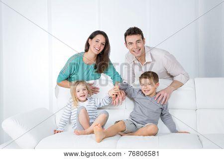Cheerful Family On White Sofa