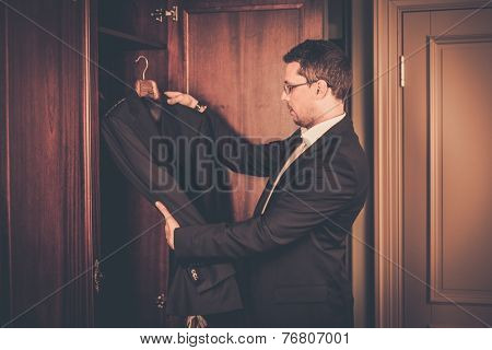 Middle-aged man taking suit from wardrobe