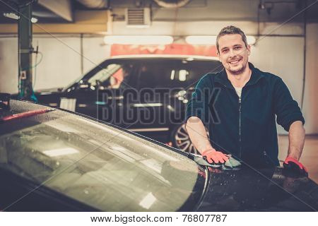 Cheerful worker wiping car on a car wash