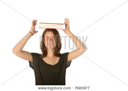 Teen balancing book on her head