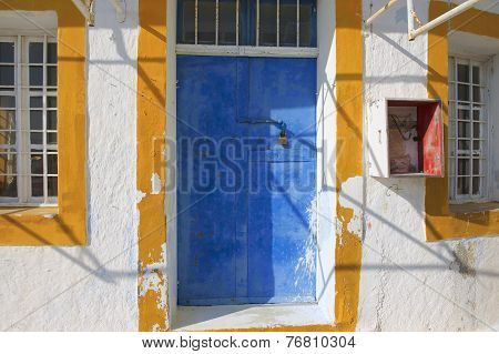 Blue painted door of an abandoned workshop in Pyrgos, Santorini, Greece.