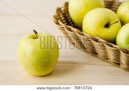 yellow wet fresh apples in a wicker basket