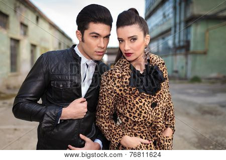 Handsome young fashion man closing his jacket, looking away while his girlfriend is holding her hands in pockets looking at the camera.