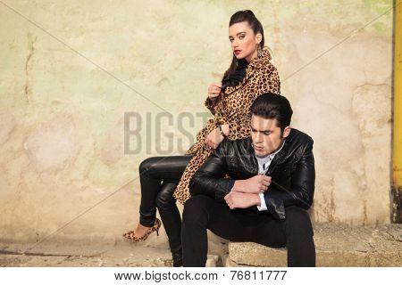 Young fashion woman sitting behind her lover, leaning on his shoulder, holding her legs crossed.