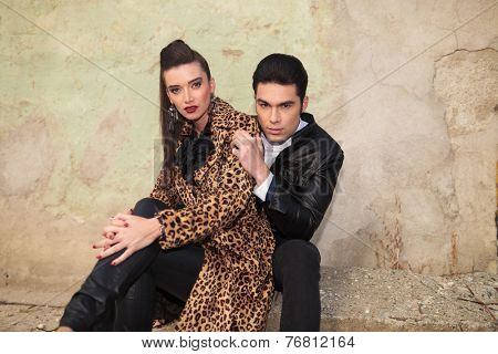 Attractive fashion couple sitting and looking at the camera. The man is holding his hand on the woman's shoulder.