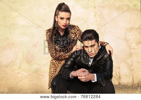 Beautiful fashion woman holding her hands on her lovers shoulders, bolt looking at the camera.