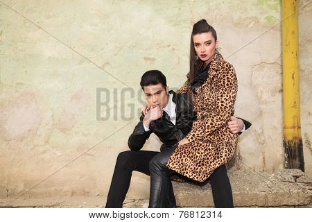 Beautiful fashion woman in a animal print coat sitting on her boyfriend lap, both looking at the camera.