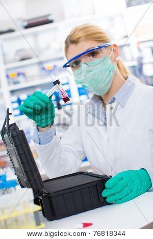 bottle of hazardous substances / ebola virus / on the hands of a woman scientist