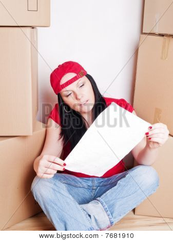 Woman Holding Plan Of House Sitting With Cartons
