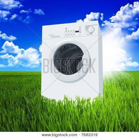 Máquina de lavar roupa e campo verde