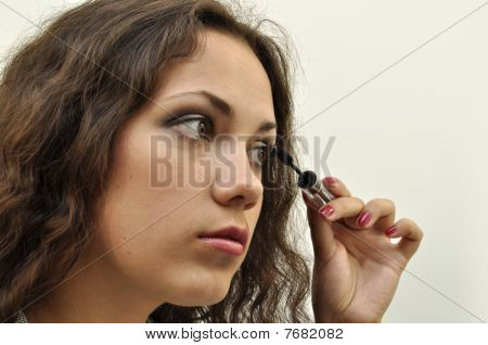 Pretty girl painting her lashes