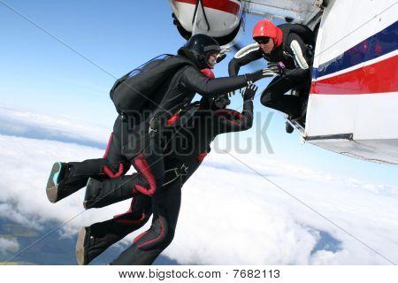 Three skydibers jump from a plane