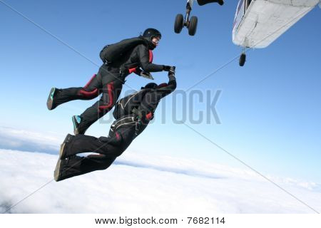 Two skydivers jump from a plane