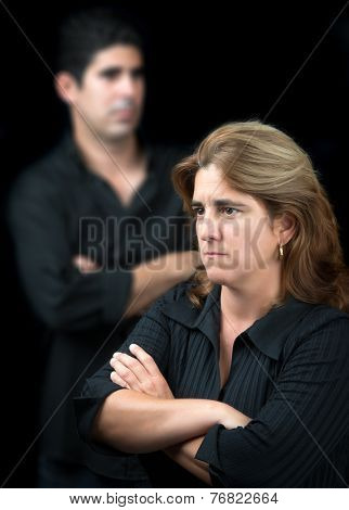 Angry and sad couple man and woman isolated on a black background