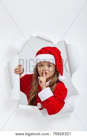 Little girl in christmas outfit telling you a secret - leaning out of a jagged edge hole