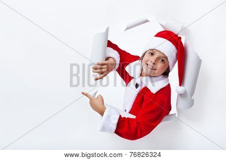 Happy Santa Claus costume boy pointing to copy space - christmas advertising