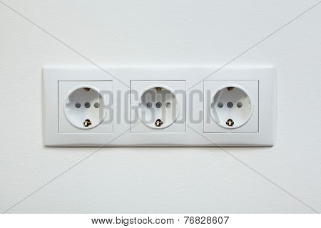 Close up photo of the white triple electric socket on the white wall.