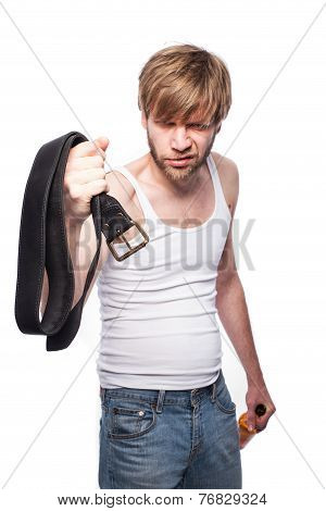 Angry man threatens with belt. Concept: Violence in the family. Abuse