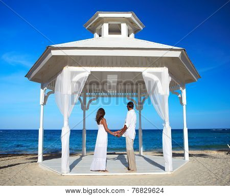 Loving couple in belvedere on the beach. Wedding.
