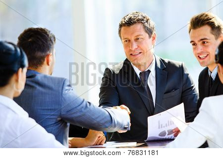 Business colleagues sitting at a table during a meeting with two male executives shaking hands