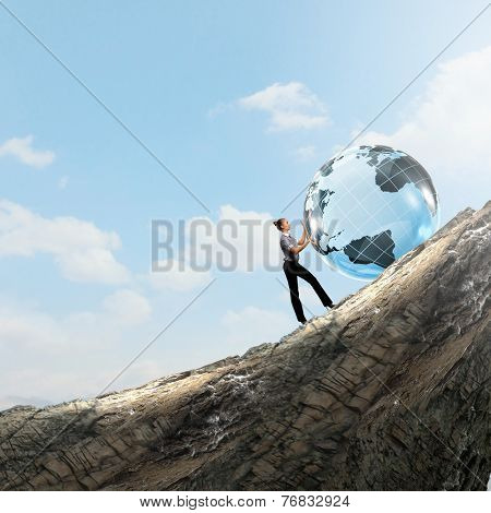 Young businesswoman rolling Earth planet up th hill