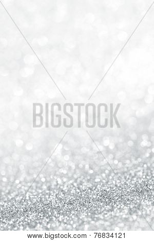 Silver festive glitter background with defocused lights