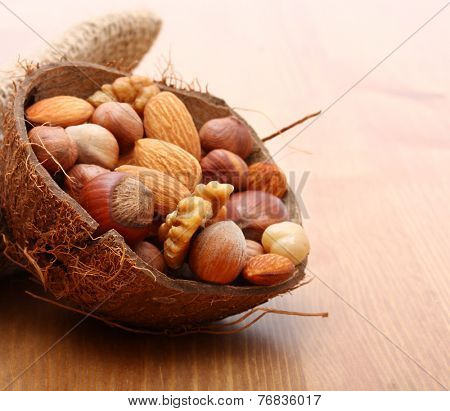 Nuts in cracked coconut on wooden background.