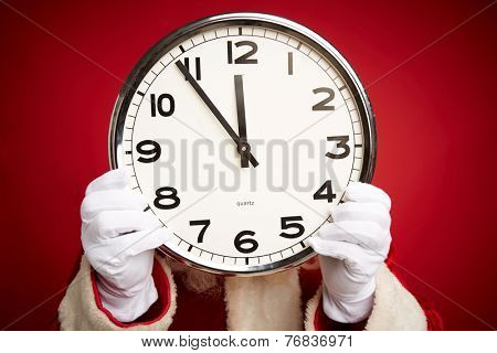 Hands of Santa holding clock with five minutes to twelve
