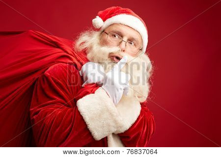 Moving Santa Claus with huge red sack keeping forefinger by his mouth