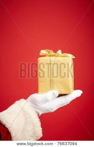 Santa Claus gloved hand with golden giftbox