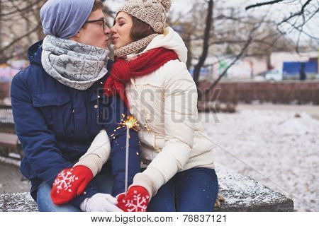 Amorous couple with Bengal light kissing in winter park
