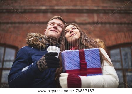 Happy young couple with giftbox and plastic glass of coffee posing outdoors