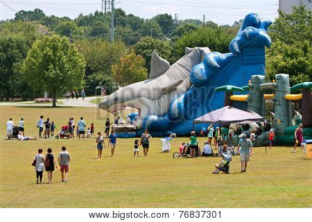 Families Enjoy A Giant Inflatable Shark Slide At Festival Playground