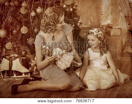 Child with mother receiving gifts under Christmas tree.