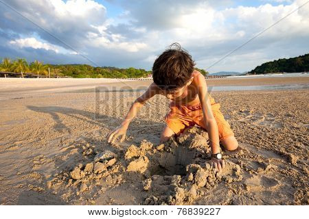 Young boy playing in the sand by the beach at sunset