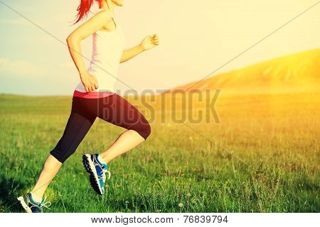 Runner athlete running on grass seaside. woman fitness sunrise/sunset jogging workout wellness conce