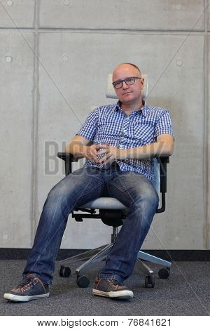 middle age balding man with eyeglasses bad sitting position on chair in office - front view