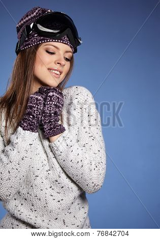 Woman with ski goggles isolated on blue