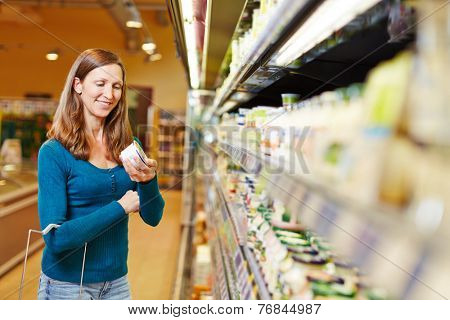 Smiling woman with shopping basket buying dairy products in supermarket
