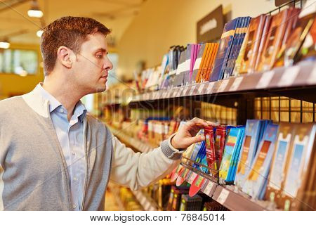 Man buying bar of chocolate in a supermarket