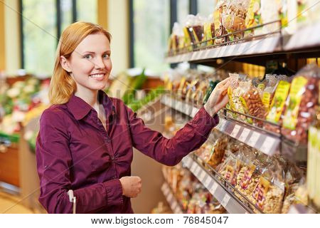 Young smiling woman buying a bag of nuts in a supermarket