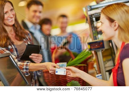 Smiling woman paying with Euro money bill at supermarket checkout