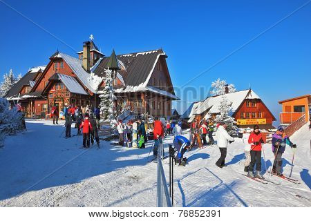 HIGH TATRAS, SLOVAKIA - JANUARY 01, 2010: Sunny morning in January at the ski resort. Skiers in bright jackets are going on a ski trip