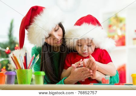 child and mom in Santa hats making christmas tree of plasticine