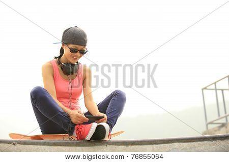woman skateboarder listening music from cellphone mp3 player on skatepark