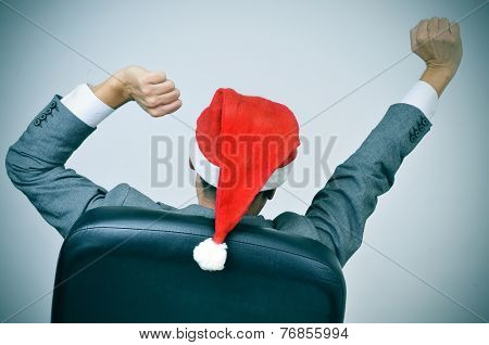 a man in suit with a santa hat stretching his arms in his office chair