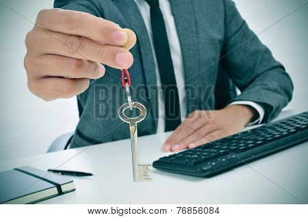 a man in suit sitting in an office desk giving the key to the observer